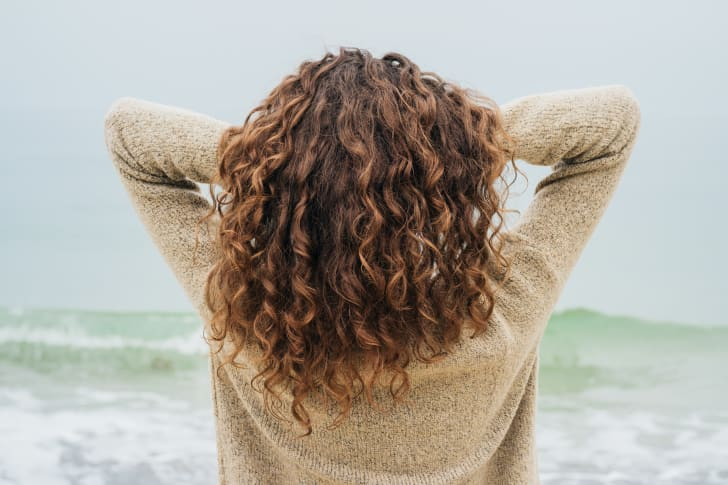 Woman with brown wavy hair facing the ocean