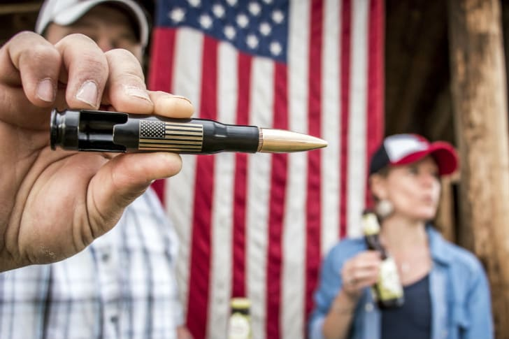 A man holds up a Bottle Breacher bottle opener made out of a decommissioned .50 caliber bullet