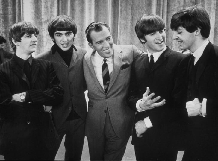 American television host Ed Sullivan smiles while standing with British rock group the Beatles on the set of his television variety series, New York, February 9, 1964. Left to right: Ringo Starr, George Harrison, Sullivan, John Lennon, Paul McCartney