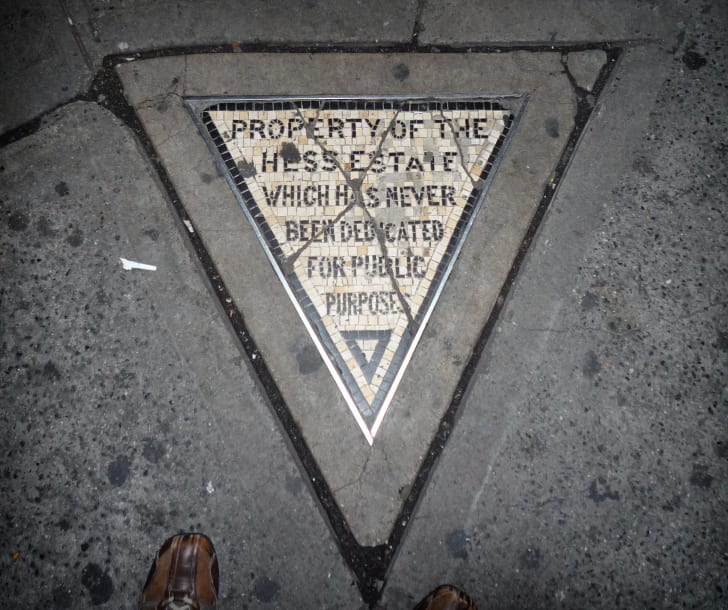 A tiled triangle in the sidewalk that reads 'Property of the Hess estate which has never been dedicated for public purpose.'