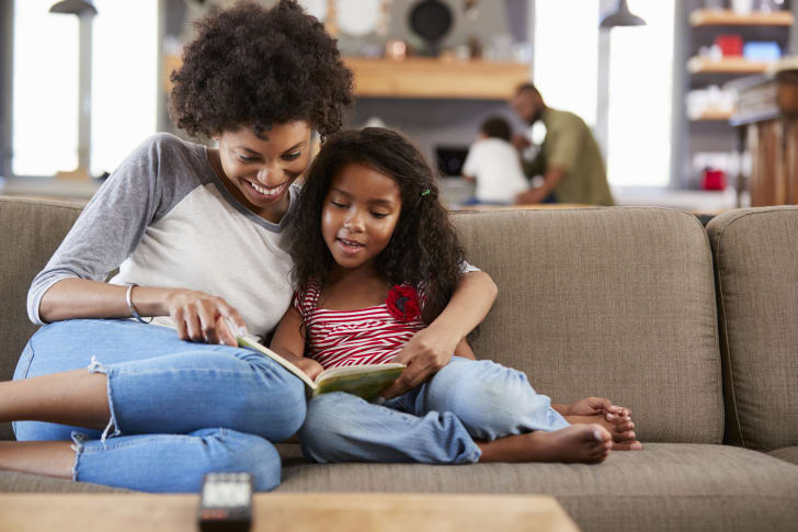 woman and girl reading book together on sofa