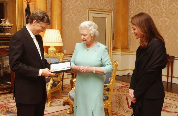 Queen Elizabeth II presents Bill Gates with an honorary knighthood in 2005. His wife, Melinda Gates, would be named an honorary dame in 2014.