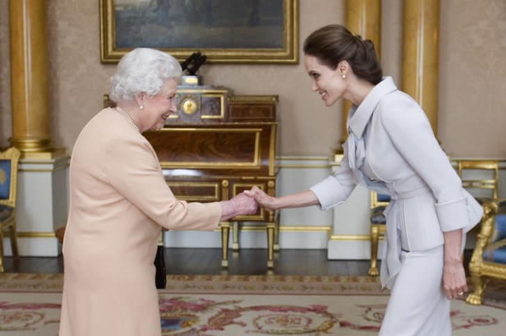 Queen Elizabeth II presents Angelina Jolie with the Insignia of an Honorary Dame Grand Cross of the Most Distinguished Order of St. Michael and St. George in 2014.