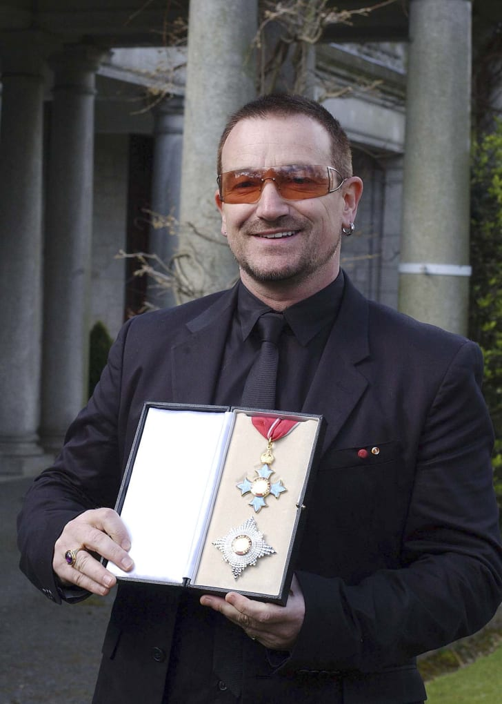 Bono poses after receiving a knighthood in recognition of his services to the music industry and his humanitarian work in 2007.