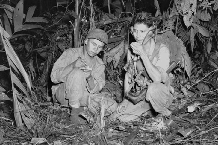 Navajo Code Talkers and Marine Corps Corporal Henry Blake Junior and Private First Class George H. Kirk operate a radio in December 1943