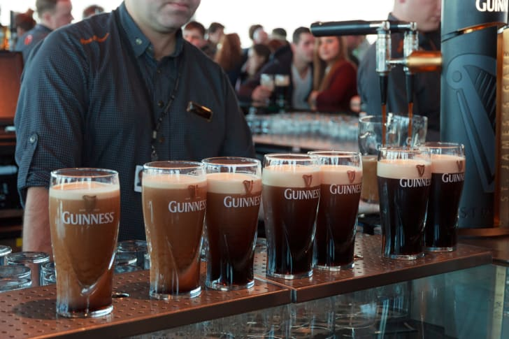 A bartender pours several pints of Guinness