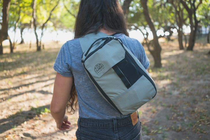 A woman walks through trees wearing a Cube Pack slung over her shoulder.
