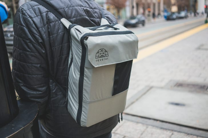A man wears a large Cube Pack as a backpack on a city street.