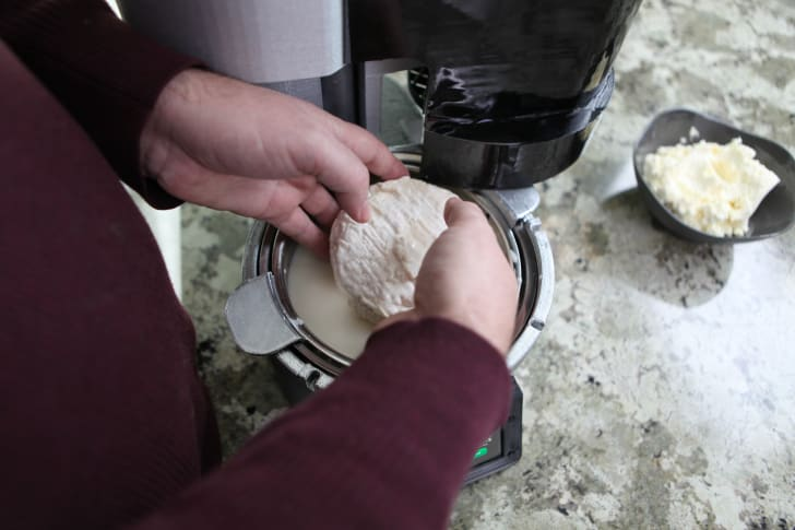Pulling cheese out of cheese-making machine.