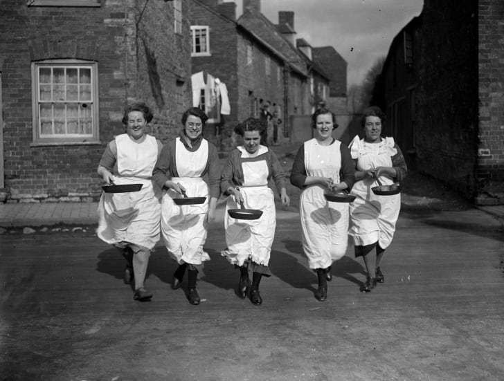 Women race while holding frying pans with pancakes