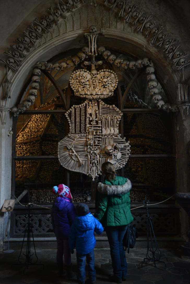 Visitors look at the coat of arms of the Schwarzenberg noble family at the Sedlec Ossuary chapel
