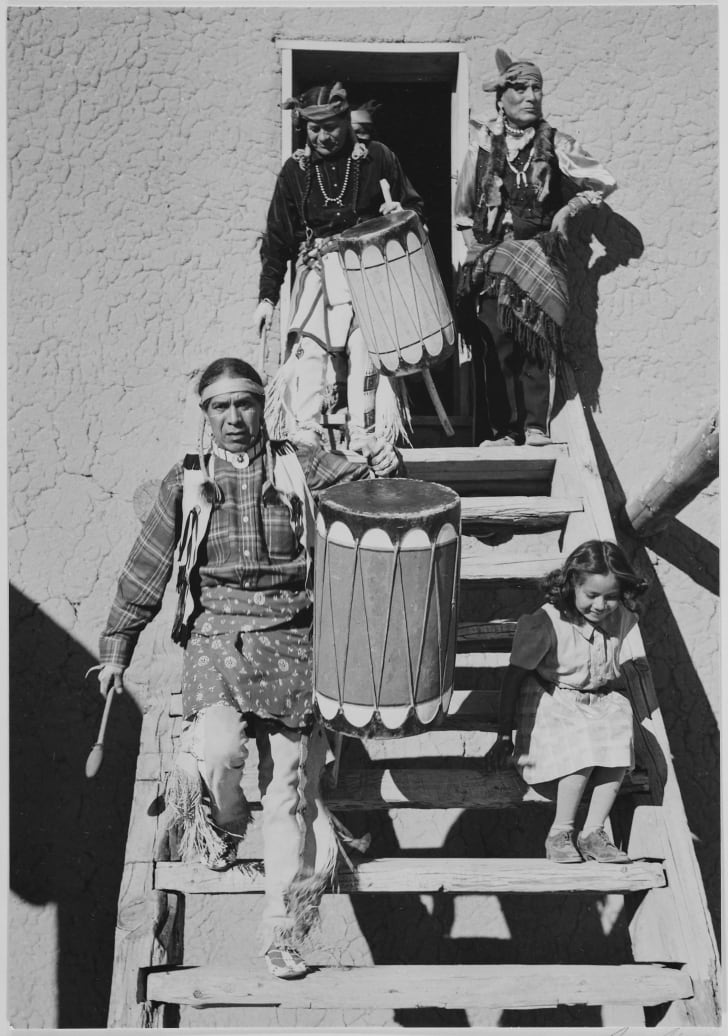 """Two Tewa descending wooden stairs, carrying drums; another Indian and child near by, """"Dance, San Ildefonso Pueblo, New Mexico, 1942."""" (vertical orientation); From the series Ansel Adams Photographs of National Parks and Monuments, compiled 1941 - 1942"""