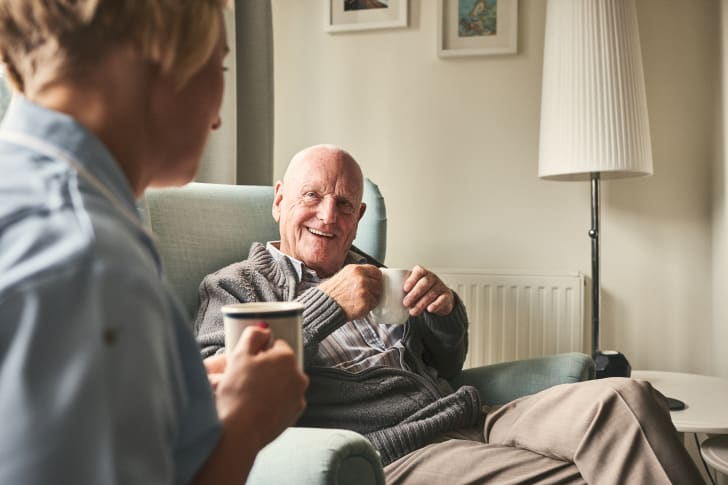 Senior man smiling and speaking with caregiver