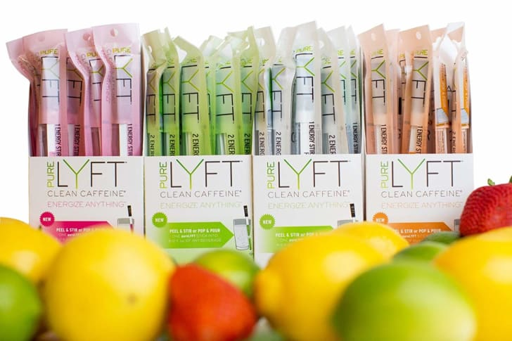 Boxes of pureLYFT stir sticks near citrus fruit