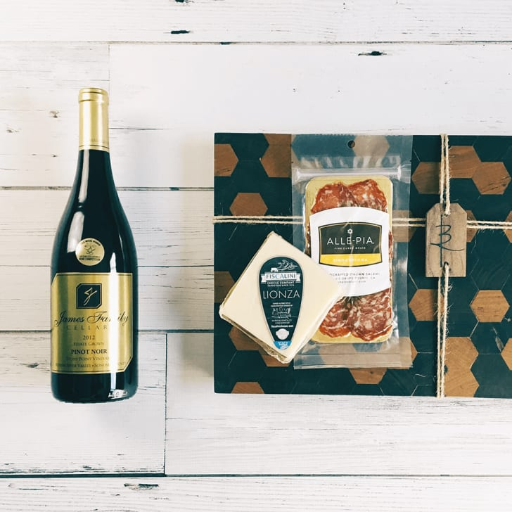 A bottle of wine next to a box of cured meat and cheese