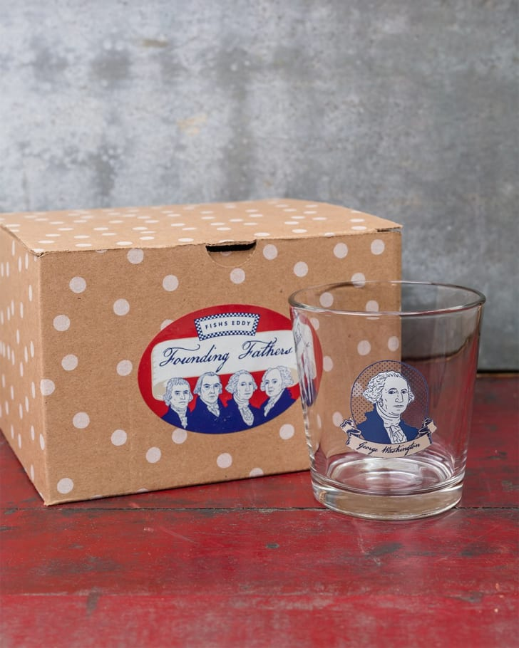 A glass with George Washington's portrait on it on a table with a box of Founding Fathers glasses