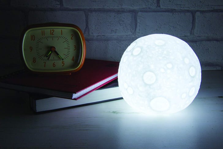 A moon-shaped lamp on a desk