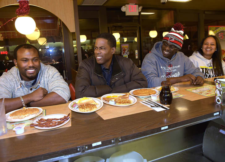 Actor Chris Rock (2nd from left) stops by the Waffle House after the VIP screening of Paramount Pictures' 'Top Five' and meets customers Donnell Woods, Daryl T. Johnson II and Semhar Haile on December 9, 2014 in Atlanta, Georgia