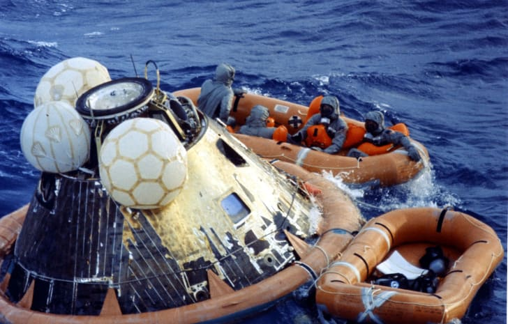 An image of the Apollo 11 astronauts getting out of their lunar vehicle into a boat on the ocean.