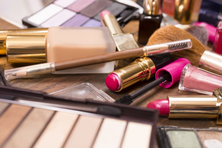Pile of beauty products on a wooden surface