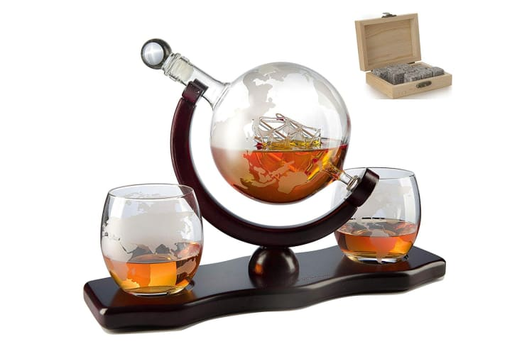 A glass decanter shaped like a globe on a stand with two glasses of whiskey