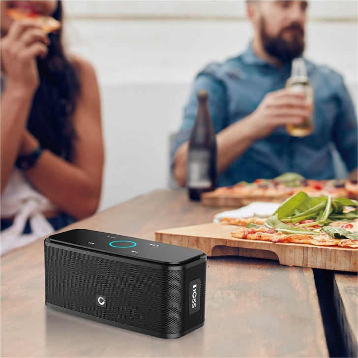 A portable speaker on a table with people eating pizza and drinking beer in the background