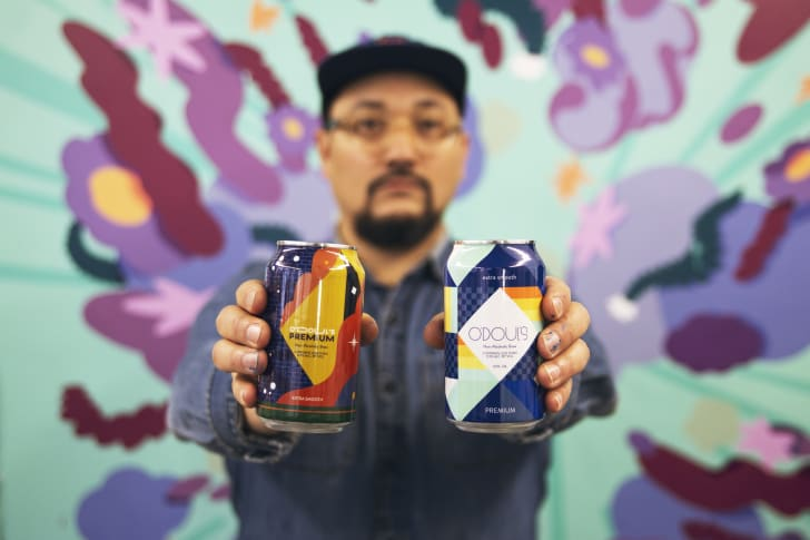 Mr. Kiji holds out his two can designs.