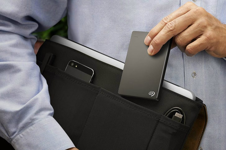 A man slips a black Seagate hard drive into a laptop bag.