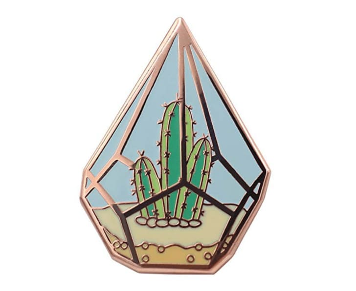 An enamel pin of a cactus in a copper terrarium