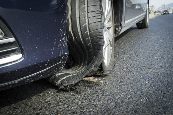 A car tire rests on the ground after a blowout