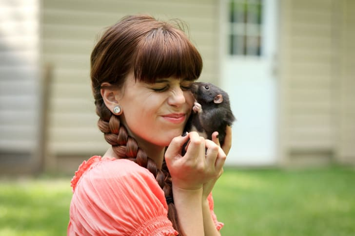 A woman plays with her pet rat