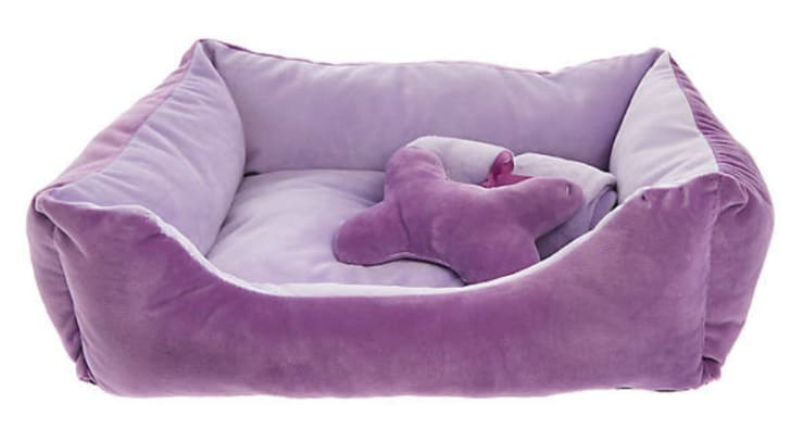 A pillow and blanket sit inside a Grreat Choice Hash Cuddler pet bed