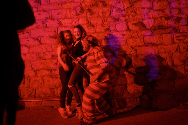 An actor scares visitors posing for a photo at 'Terror Behind the Walls' in Philadelphia