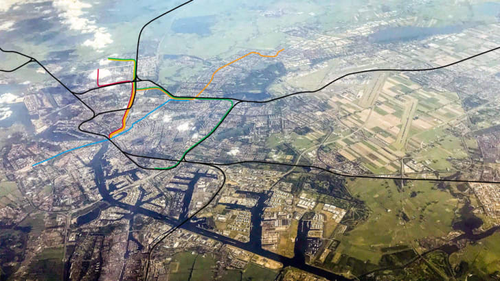 An aerial photo of Amsterdam with subway lines represented by colored lines