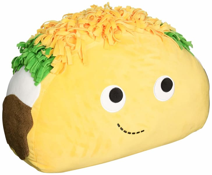 A cute taco pillow with a happy face on it.