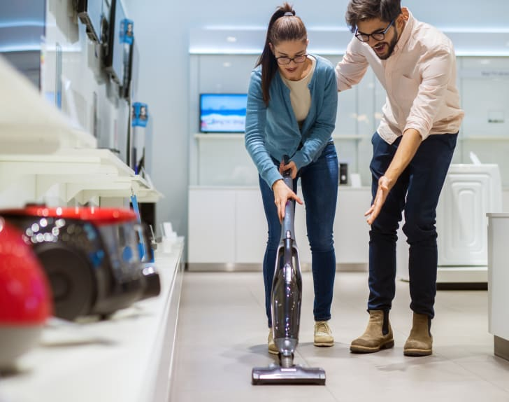 A woman tries out a stick vacuum at a store