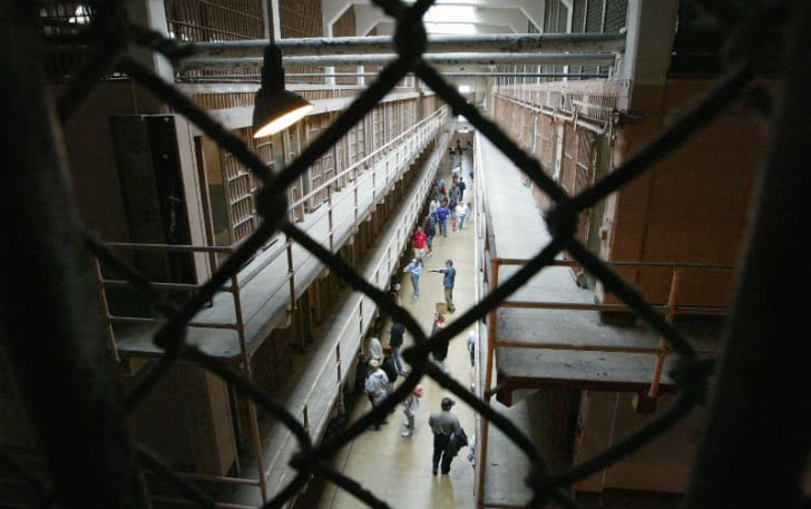A camera peers through a chain-link fence inside Alcatraz