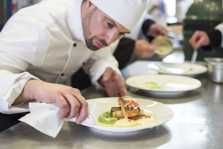 A chef staring intently at a dish of salmon