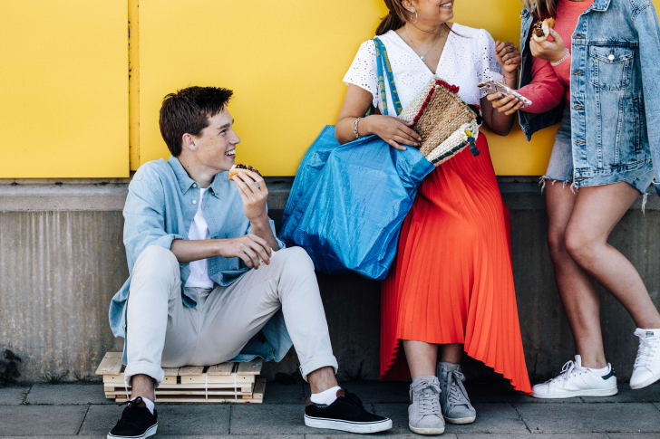 Three young people eat hot dogs outside of an IKEA store.
