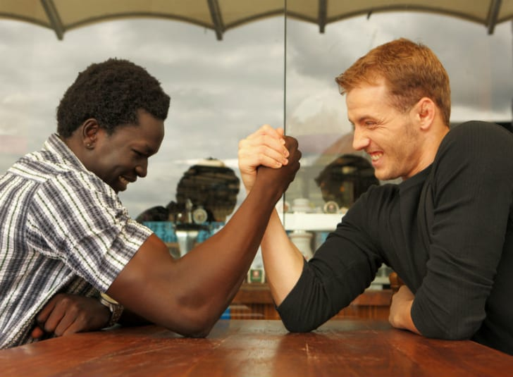 Two men engage in an arm wrestling match