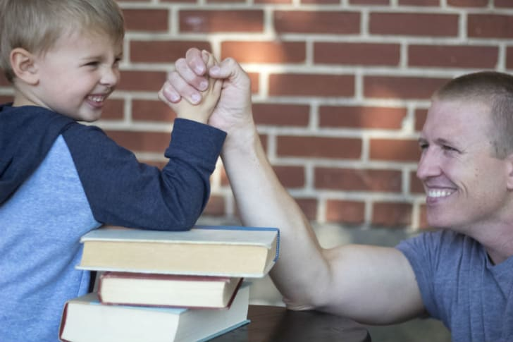 A child uses books to help in arm-wrestling an adult