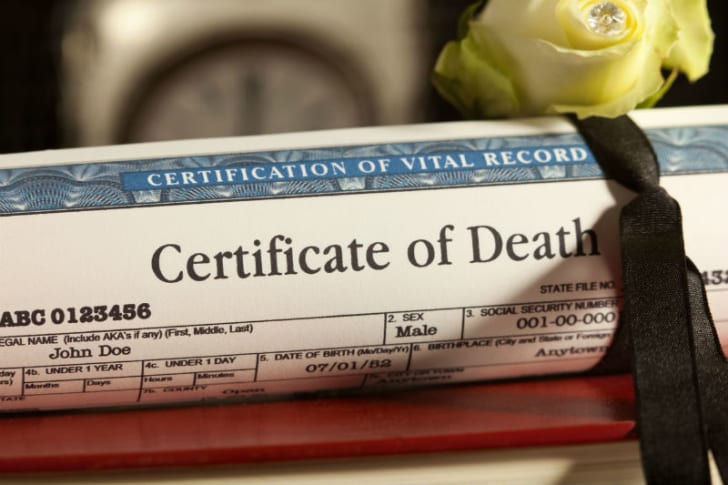 A death certificate sits on top of a table