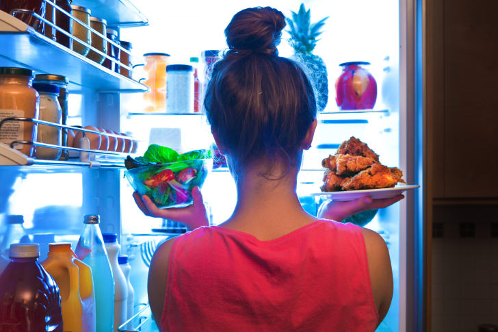 Woman pulling food out of a fridge.