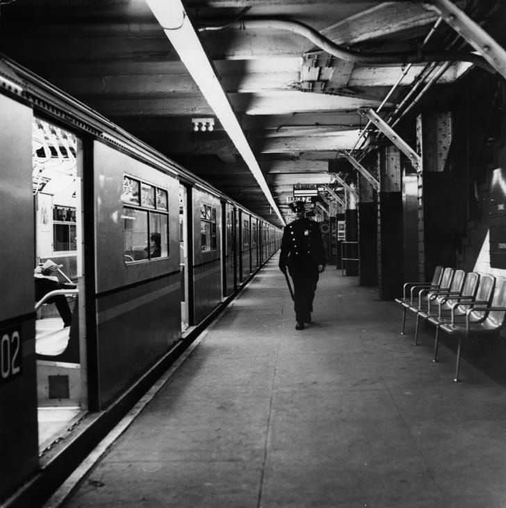 A policeman patrolling an empty New York subway station