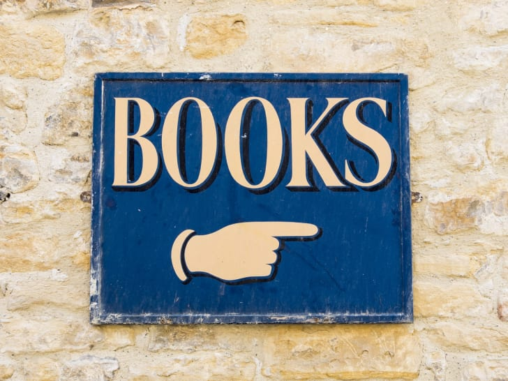 "A blue sign with white letters spelling out the word ""books"" and a hand pointing"