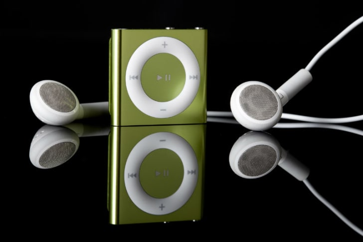 The iPod Shuffle rests near a pair of headphones