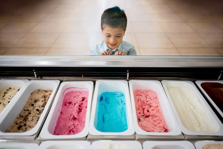 image of a child looking at the flavors inside an ice cream counter