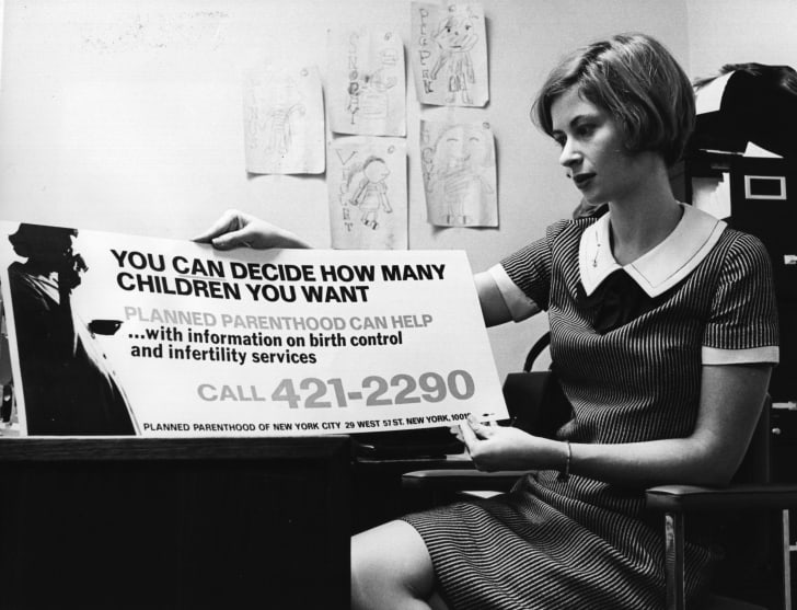 Planned Parenthood's publicity director looks over a poster in 1967.