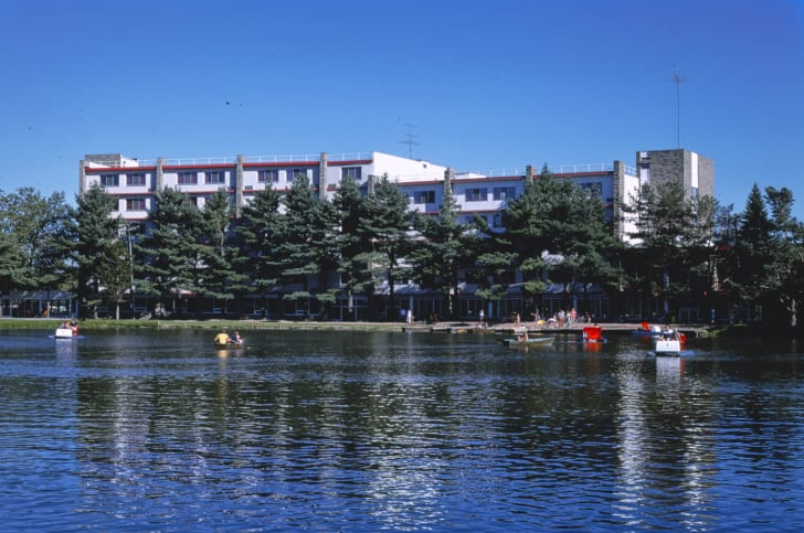 People rowing boats across a lake in front of a resort