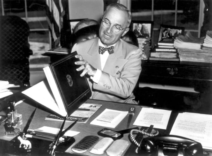 Harry Truman examines paperwork while sitting behind a desk
